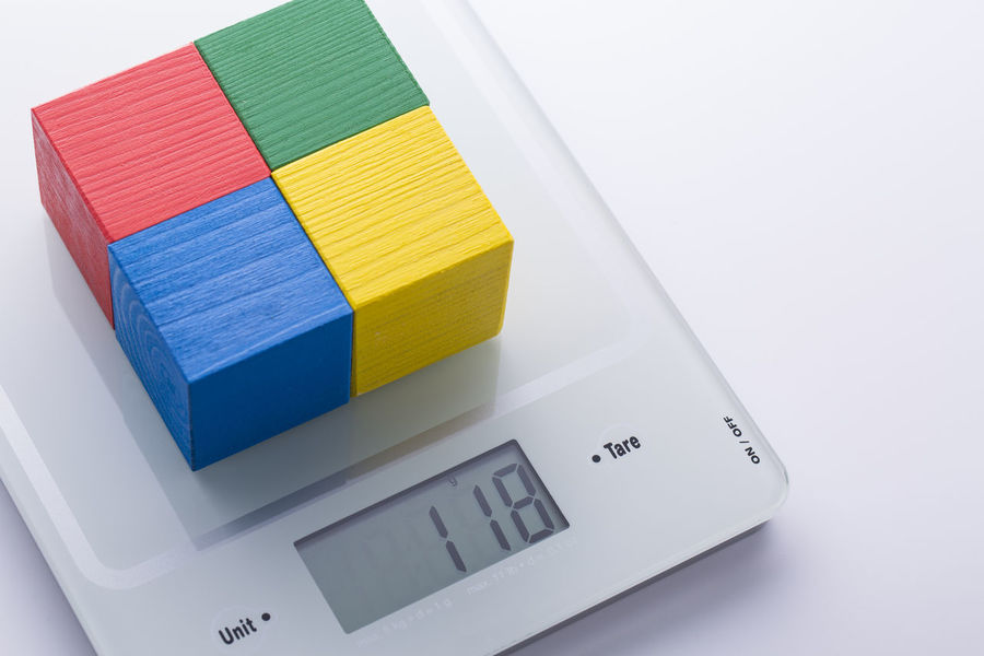 Digital kitchen scale with colorful cubes on it. Proper nutrition and ingredient control metaphor. Balance Close-up Colored Control Cube Data Digital Health Healthy Eating Ingredient Kitchen Measurement Multi Colored No People Nutrition Proper Scale  Stack White Background