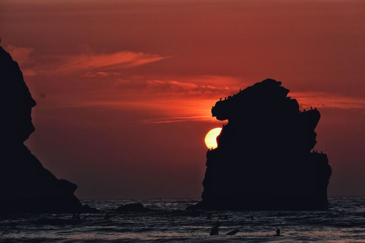 Silhouette rock formation in sea against sky during sunset