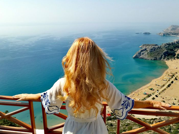 Rear View Of Woman With Blond Hair Looking At Sea During Sunny Day