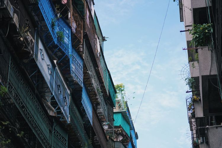 Low angle view of hanging amidst buildings against sky