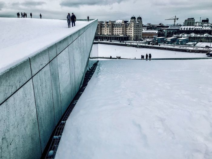 People On Snow Covered Bridge In City