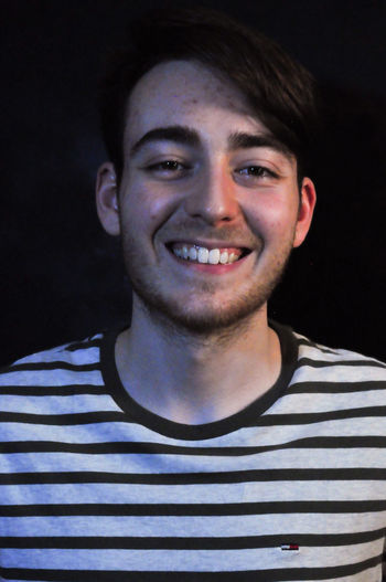 Portrait Headshot Front View Striped Looking At Camera One Person Happiness Casual Clothing Smiling Emotion Young Adult Toothy Smile Teeth Indoors  Young Men Men Lifestyles Males  Close-up Black Background Human Face Teenager
