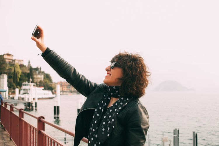 Side view of smiling woman taking selfie by sea against clear sky