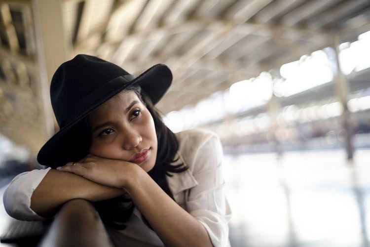 Portrait of beautiful woman sitting in hat