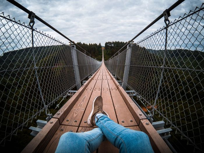 Low section of woman relaxing on footbridge against sky