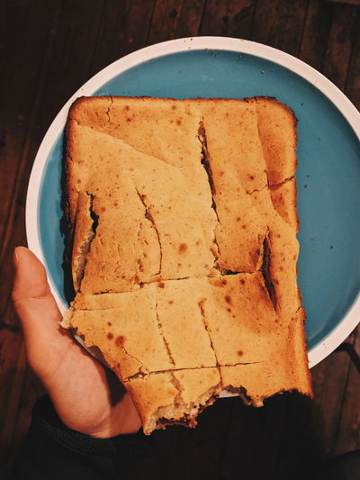 High angle view of hand holding banana bread in plate
