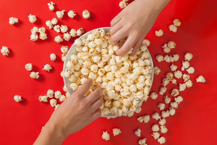 Two hands grabbing for fresh popcorn Movie Time Bowl Directly Above Food Food And Drink Human Body Part Human Hand Indoors  Movie Theater People Popcorn Real People Red Red Background Snack Studio Shot Women