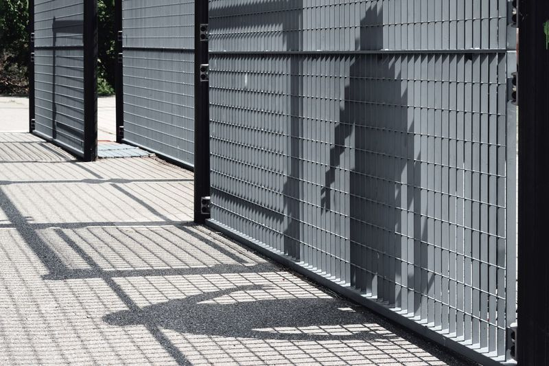 Shadow Play Shadow Fence Silhouettes One Person People Geometry Hand Human Body Part City Pattern Protection Architecture Building Exterior Built Structure Paving Stone Pavement Focus On Shadow Long Shadow - Shadow The Still Life Photographer - 2018 EyeEm Awards The Creative - 2018 EyeEm Awards