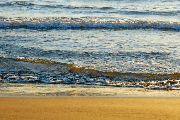 Waves rushing towards shore in a golden sea