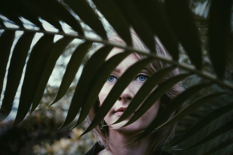 Close-up portrait of woman seen through leaves