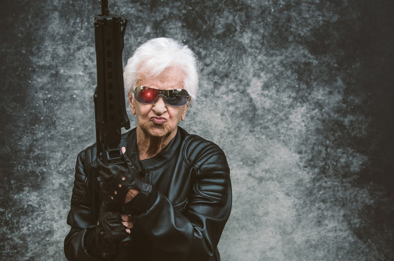 Portrait of senior woman holding rifle against wall