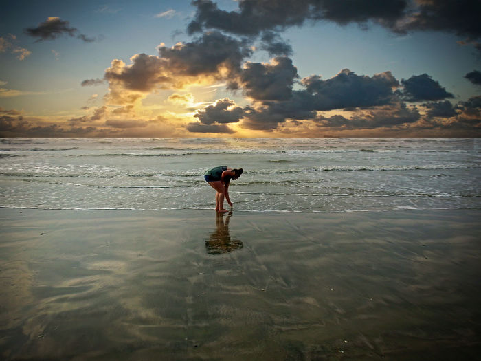 Teenage girl standing on shore at beach
