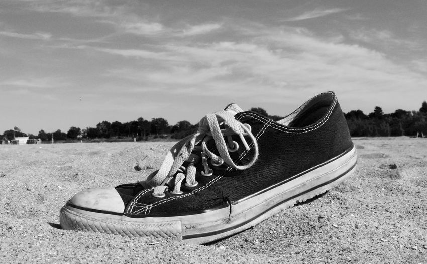 Close-up of shoe on beach against sky