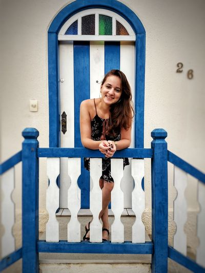 Portrait of smiling young woman standing outside house