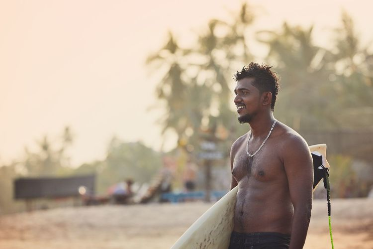 Young man holding surfboard looking away at beach