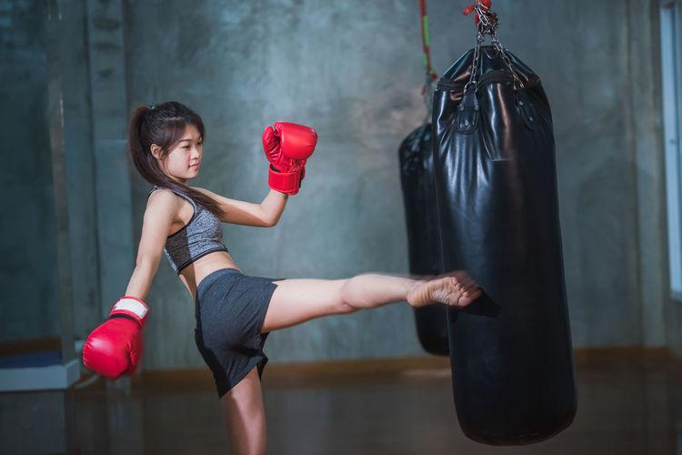 Female boxer kicking punching bag