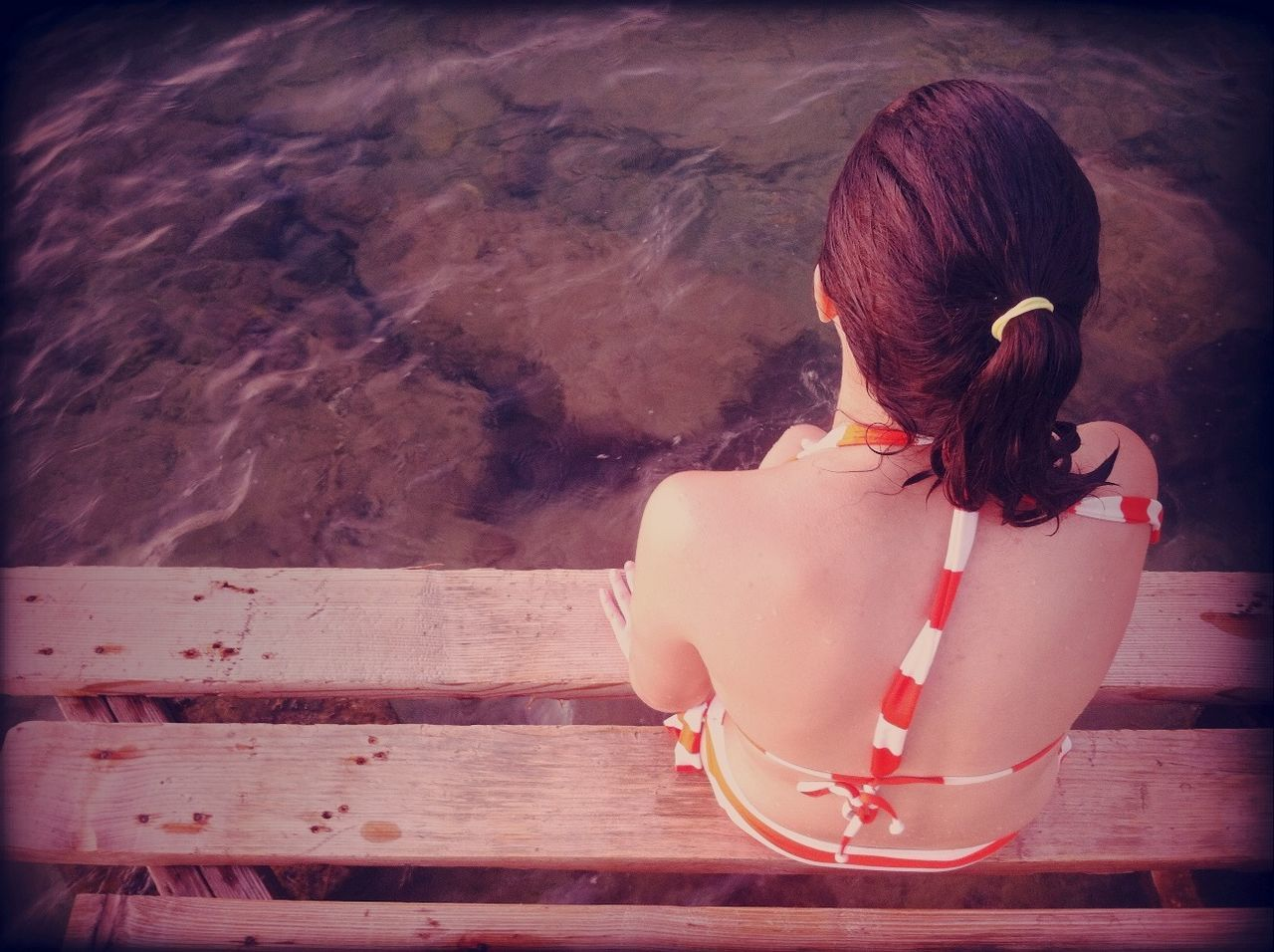 A young woman seen from behind sitting on a dock with her feet in the water