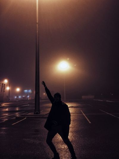 Silhouette Man Standing Arms Outstretched On Wet Street At Night