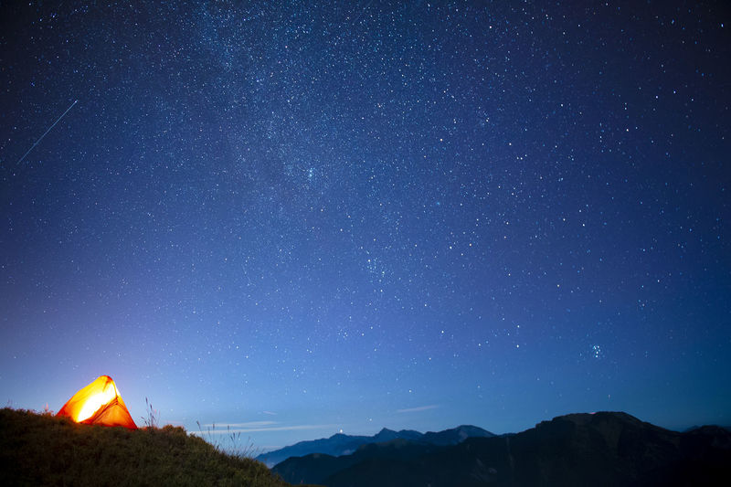 Low angle view of illuminated mountain against star field