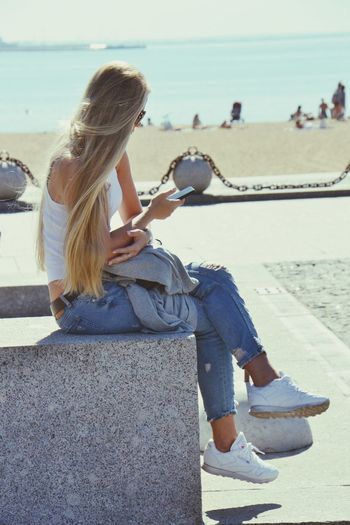Long, blonde haired young woman, using smartphone near the beach at park in St. Petersburg, Russia. Sitting Beach Relaxation Sea Casual Clothing One Person Young Adult Adult Wireless Technology Vertical Sunlight Sand Water's Edge One Woman Only Water