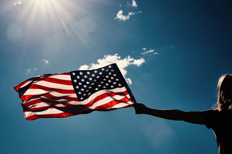 American flag outdoors. woman silhouette holds usa national flag against blue cloudy sky. 4th july