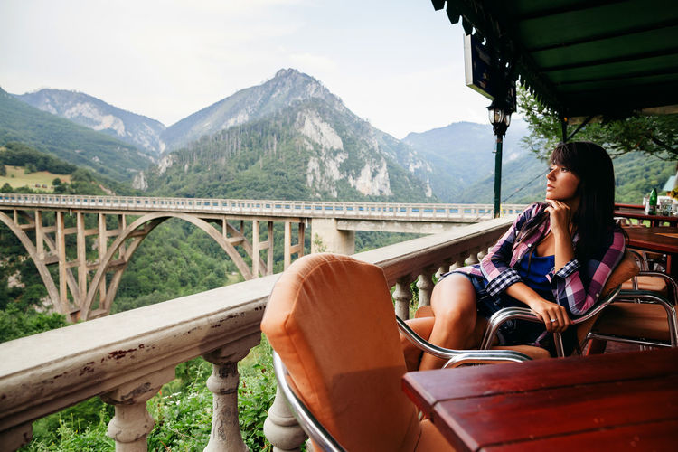 Mid adult woman looking at mountains while sitting on chair