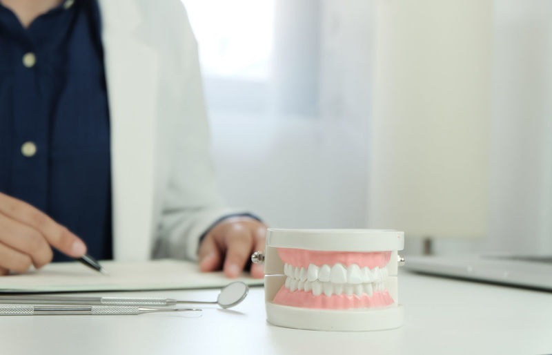 Midsection of dentist working with dentures in foreground at desk