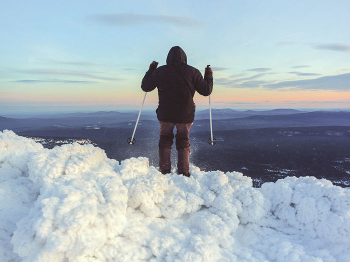 Rear view of man standing on snow covered shore against sky