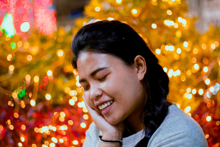 Smiling young woman against illuminated christmas tree at night