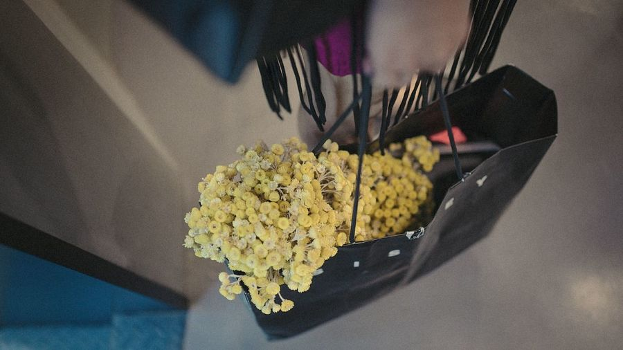 Cropped Image Of Person Holding Bag With Yellow Flowers At Home