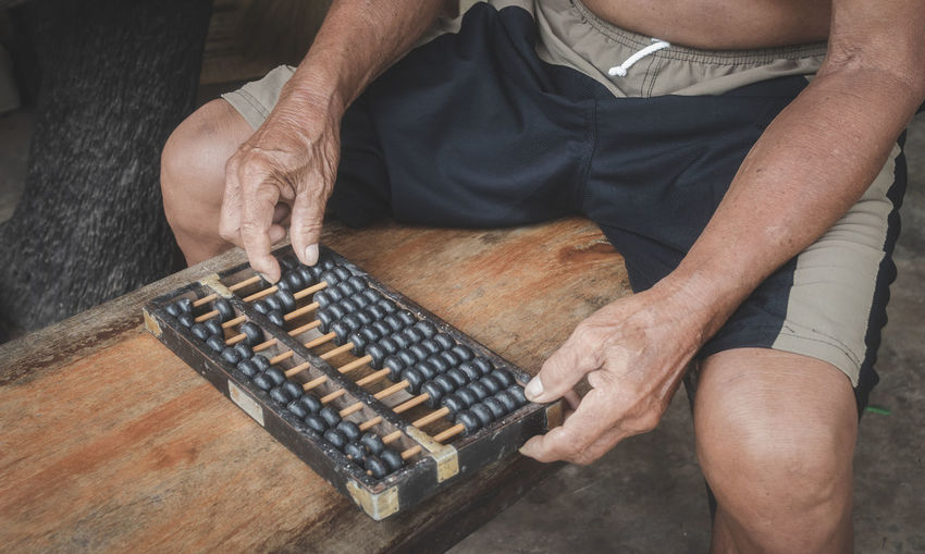 Midsection of man playing with abacus