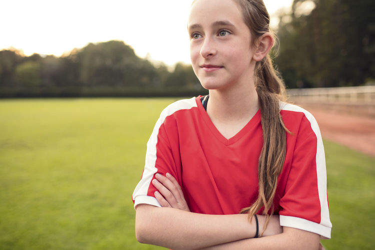 Portrait of teenage girl standing on field