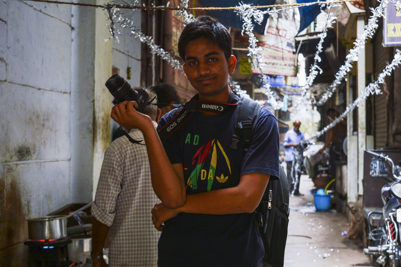 Portrait of a smiling young man holding camera
