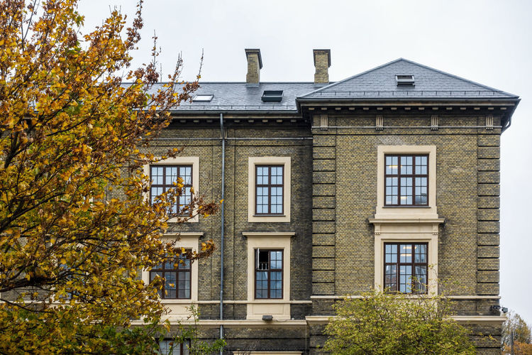 Low angle view of building against autumn leaves from foreground tree.
