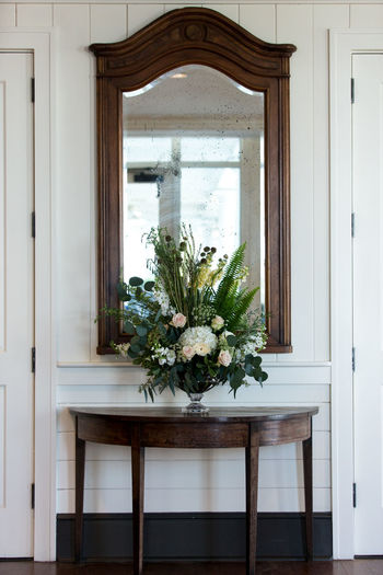 Flower vase on wooden table against mirror at home