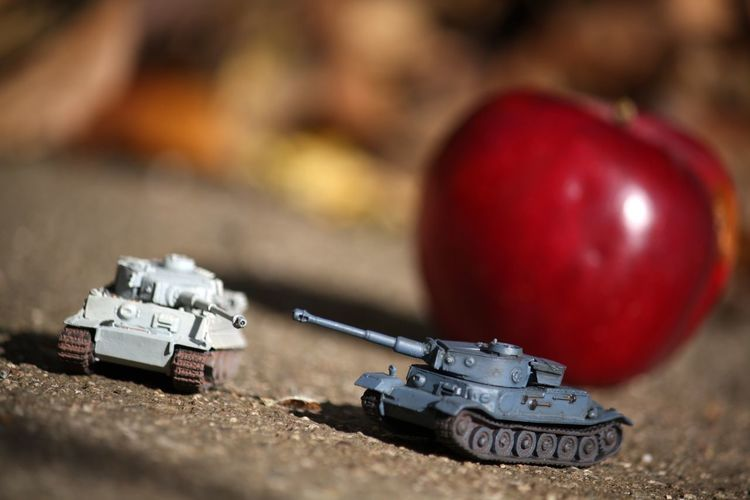Close-Up Of Armored Tanks Against Apple On Footpath