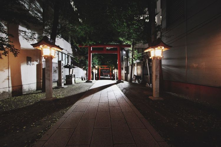 Torii Gate On Footpath Amidst Buildings