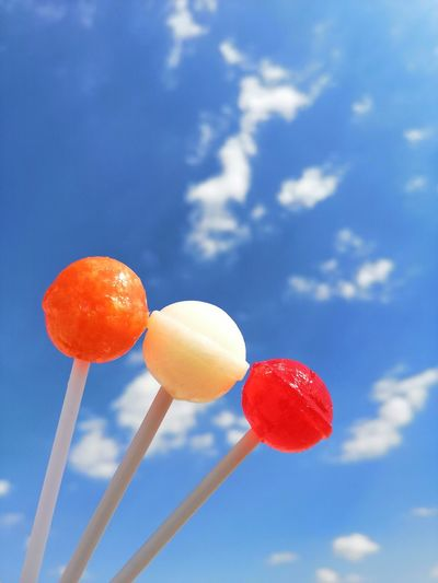 Low angle view of oranges against blue sky