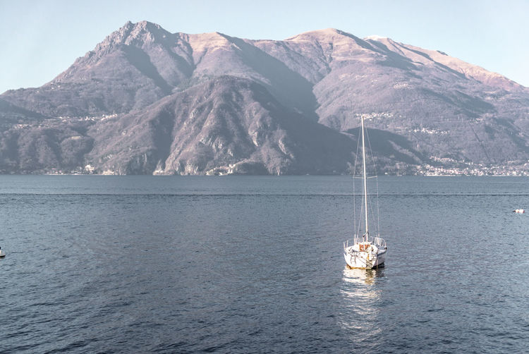 Sailboat in sea against mountains