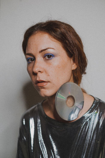 Portrait of young woman with compact disk against wall