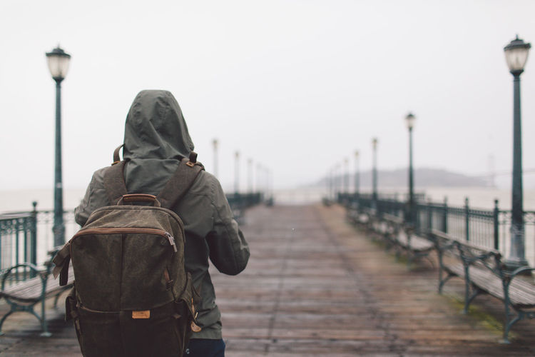 Rear View Of Young Woman With Backpack Walking On Pier Against Sky