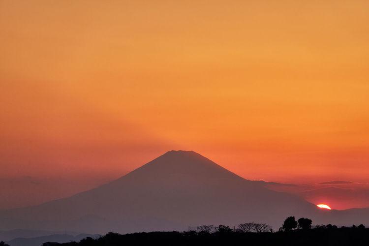 Scenic view of silhouette volcano mountain against orange sky
