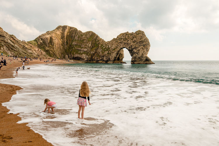 Children play on the beach and in the small waves in the foreground of the tourist attraction Durdle Door, a limestone arch along the Jurassic Coast, Dorset, England. Beach Blue Sea British Seaside Coast Dorset Durdle Door South Coast. South England Staycation Arch Bay Children Children Playing Cliff Face Cliffs Coastline Cove Family Holiday Famous Attraction Golden Sands Jurassic Coast Natural Arch Playing Rock Pinnacle Tourism Tourist Attraction  Water Sea Sky Land Beauty In Nature Real People Scenics - Nature Cloud - Sky Lifestyles Child Rock Women Nature Childhood Girls Two People Rock - Object Day Horizon Over Water Outdoors