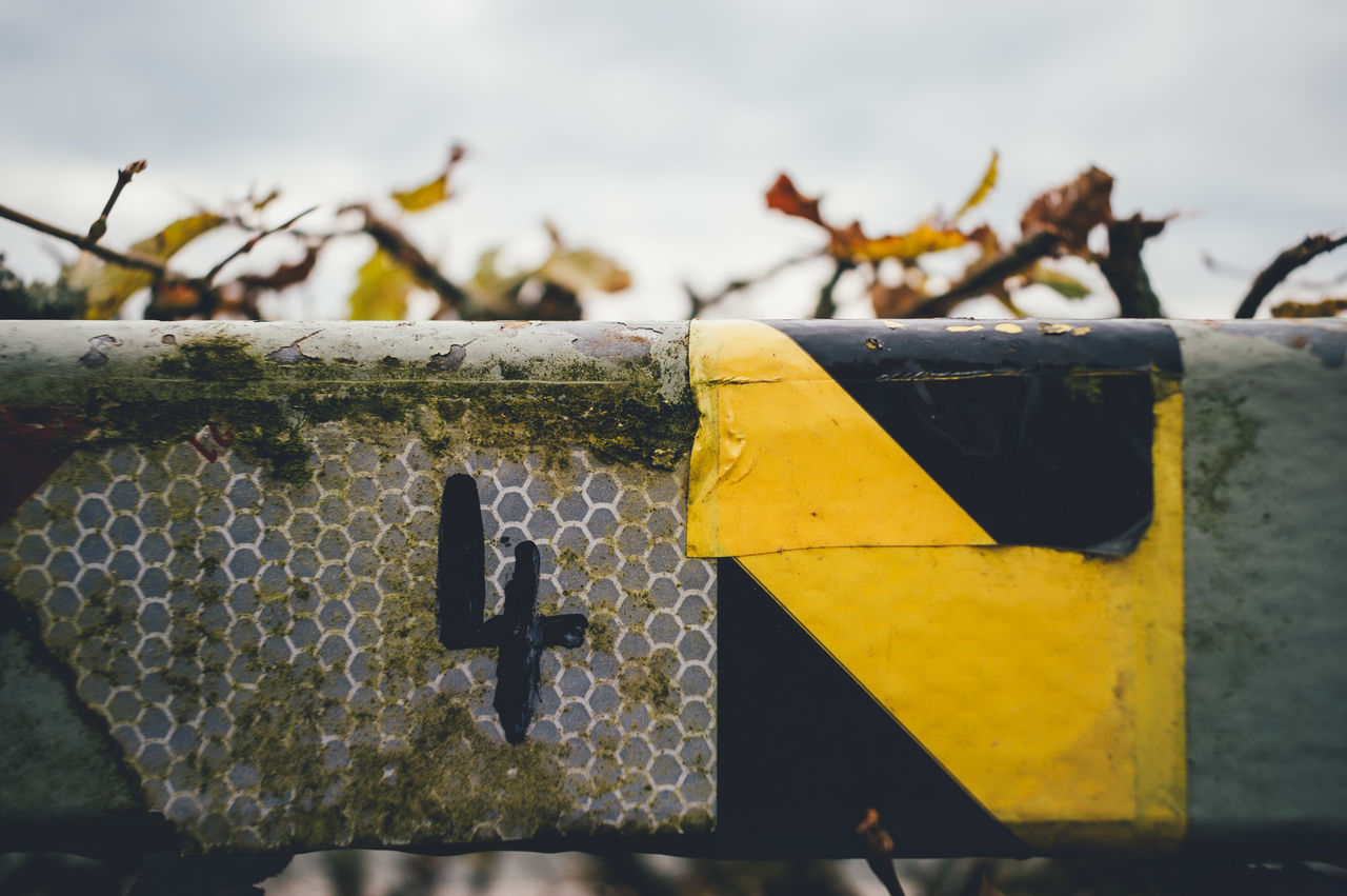 Close-Up Of Number 4 On Fence Against Sky