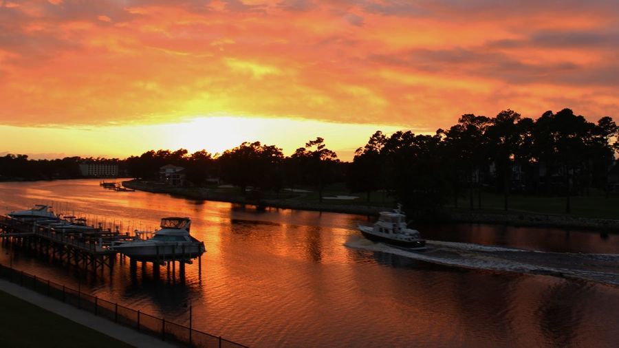 Vibrant, colorful sunset reflecting in the intracoastal waterway in Myrtle Beach, South Carolina. Bright orange, purple and yellow sky. Orange Sky Sunset Glow Beauty In Nature Boat Wake Boats In The Bay Cloud - Sky Colorful Sky Intracoastal Water Way Scene Landscape Sunset Nature Nautical Vessel No People Orange Color Outdoors Purple Sky Reflection Reflection In The Water Silhouette Sky Sunset Sunset Reflection Tranquility Tree Water Waterfront