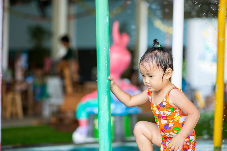 Close-up of cute girl standing at water park