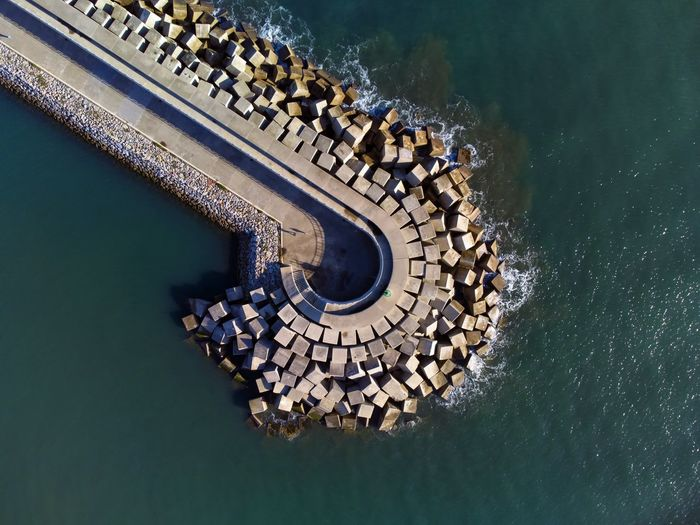 Aerial view of cement blocks protecting the shore from the waves in the port of luanco in asturias,.