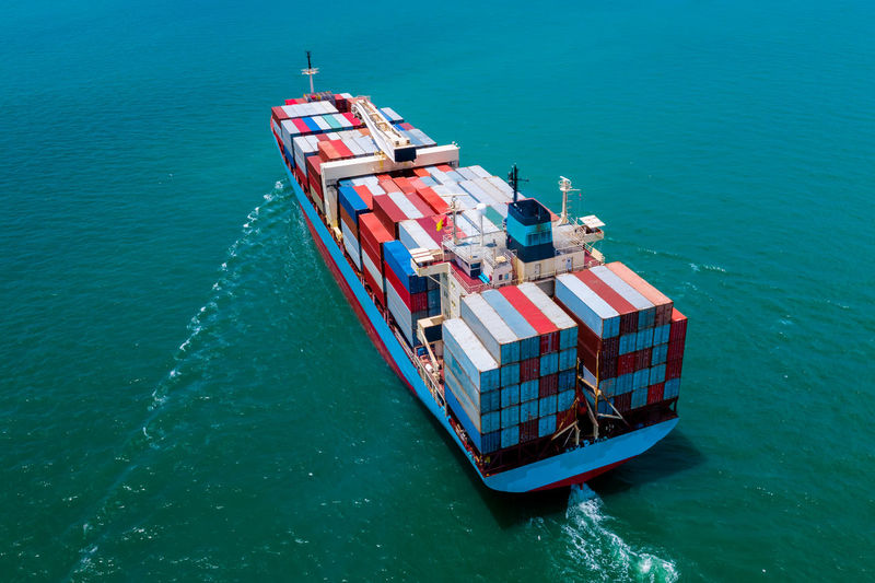 High angle view of shipping containers sailing on sea