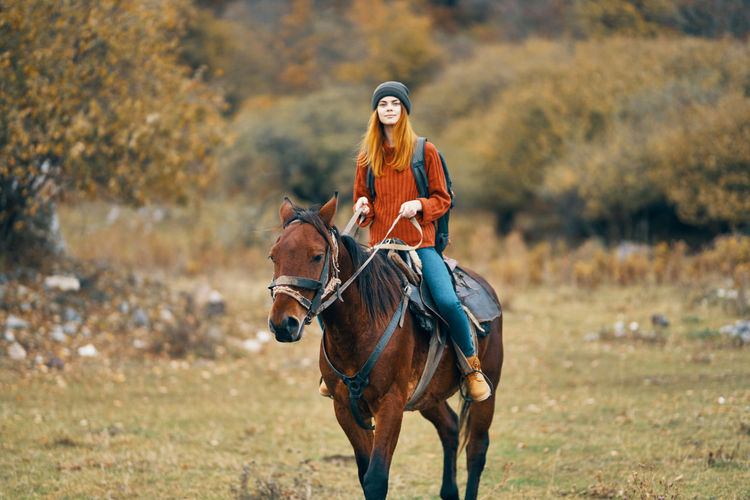 Portrait of young woman riding horse on land