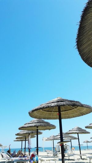 Scenic View Of Tourist On Beach Resting Under Umbrella Against Clear Sky